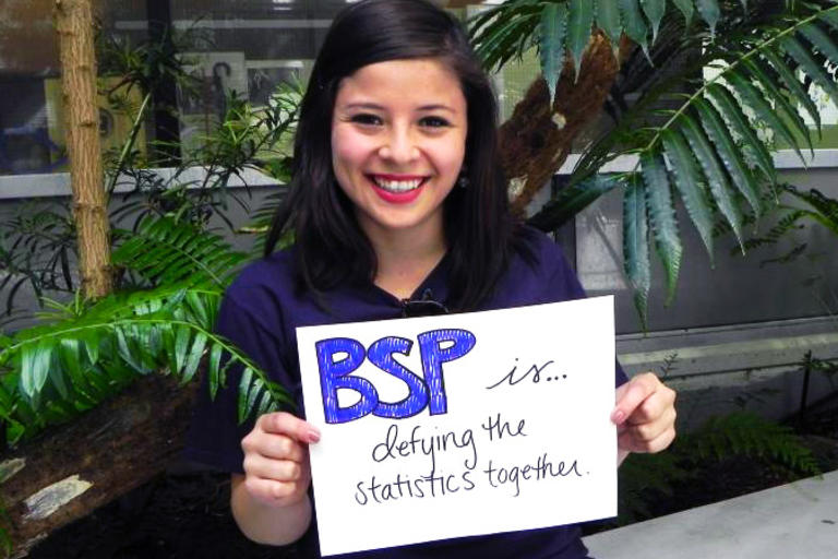 "Student holding sign that reads ""BSP is...defying the statistics together"""