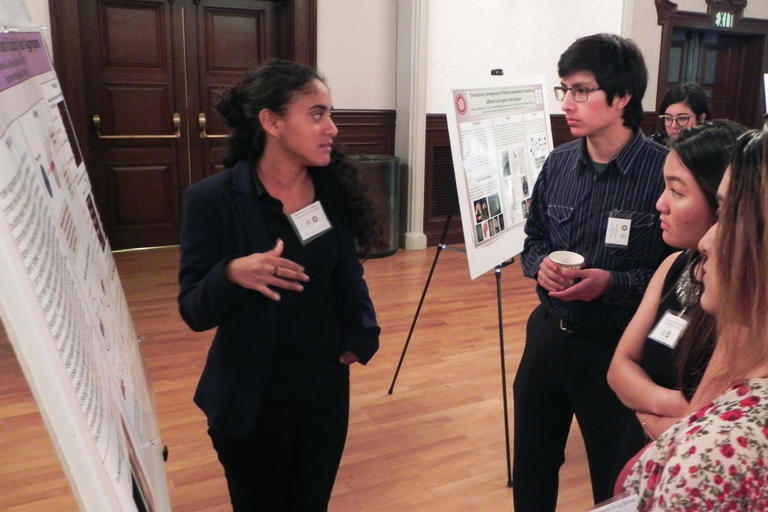 BSP Student explaining her research poster to symposium attendees.