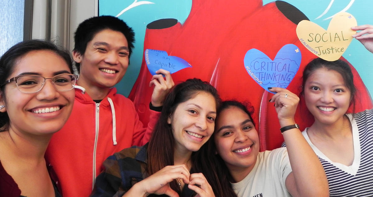 Students posing with paper hearts with their quotes.