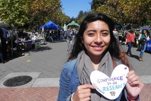 "Student holding a paper heart that reads ""Confidence to do Research"""